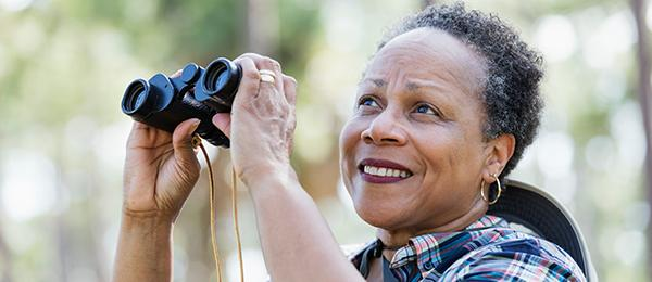 woman holding binoculars - welcome to retirement